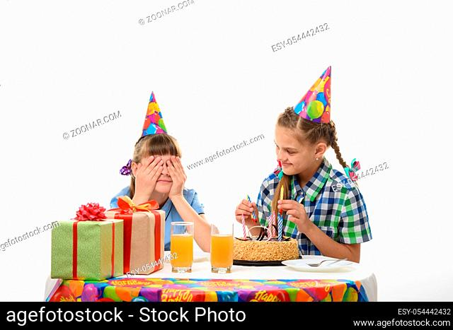 One girl covered her eyes with her hands, the other inserts matches in a birthday cake