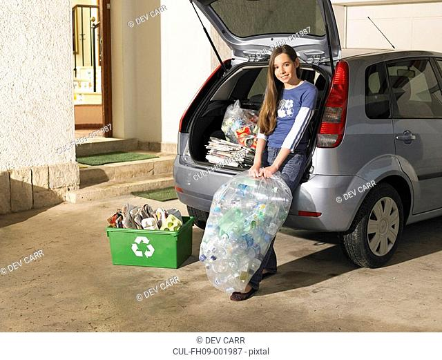Girl 12-14 leaning on car holding recycling box, portrait