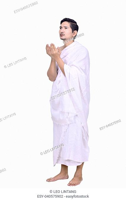 Religious asian muslim man with hajj dress pray isolated over white background