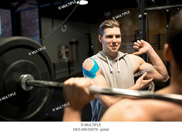 Personal trainer guiding man weightlifting barbell at gym