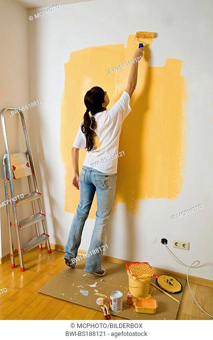 Young woman paints a white wall with orange colour
