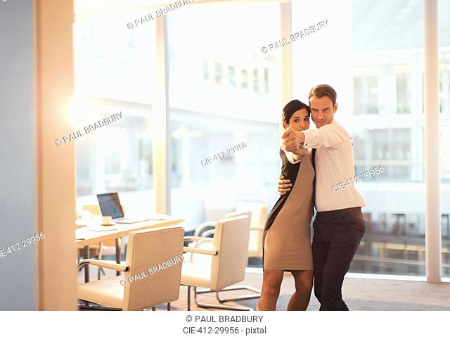 Businessman and businesswoman dancing in conference room
