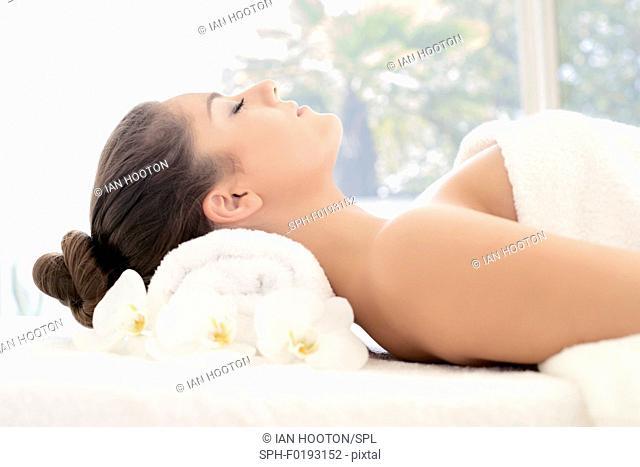 Woman lying on towel in spa