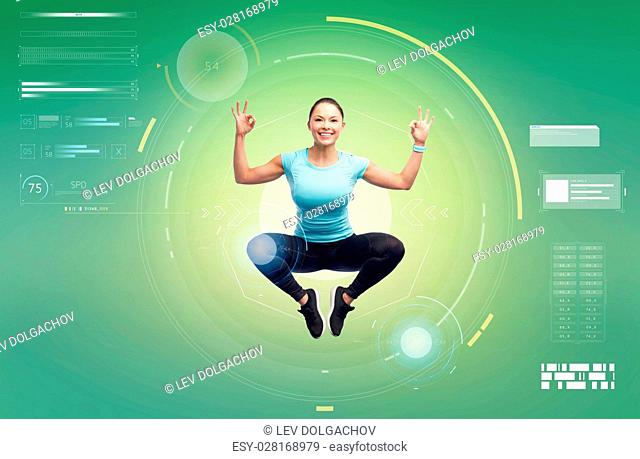 sport, fitness, motion, technology and people concept - happy smiling young woman jumping in air and showing ok hand sign over white background