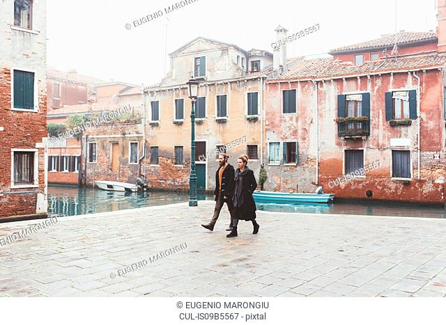 Couple strolling by canal waterfront, Venice, Italy