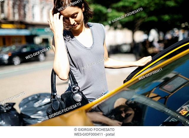USA, New York City, young woman getting on a yellow cab