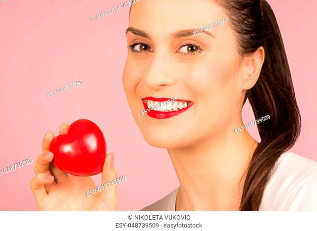 Beautiful smiling woman is holding a red heart, love and Valentines day concept