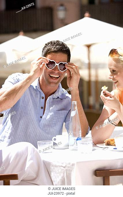 Laughing man wearing heart-shape sunglasses at sunny, outdoor cafŽ