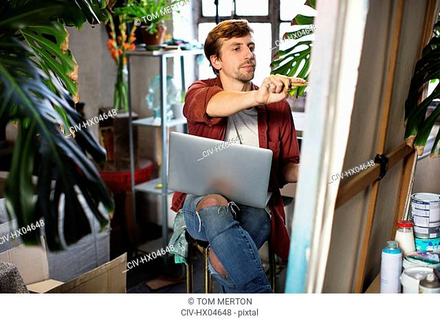 Male artist painting and using laptop in apartment