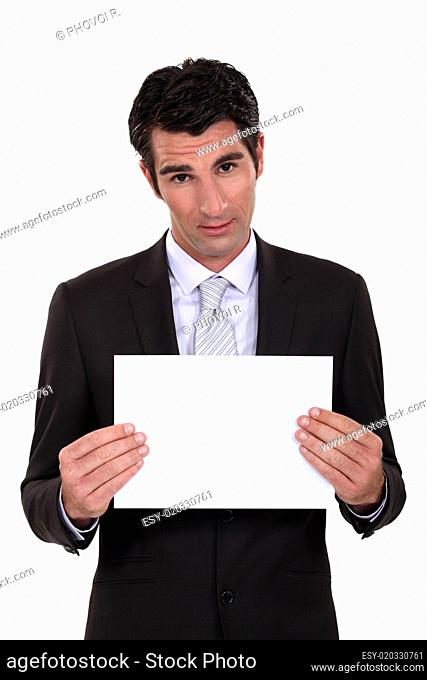 Man in suit showing blank sheet of paper