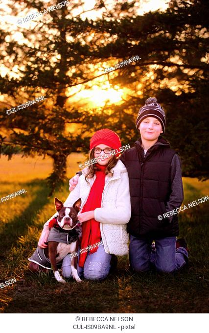 Portrait of girl and boy, with boston terrier dog, outdoors