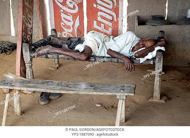 Mature man resting on a charpoy in Achrol Village - Jaipur District, Rajasthan, India