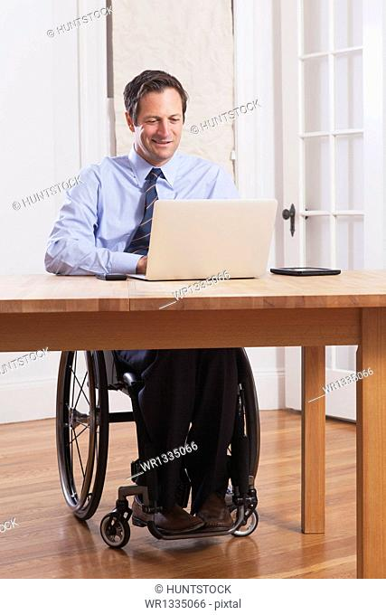 Businessman with spinal cord injury in a wheelchair working on laptop