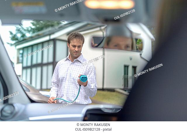 Man charging electric car, seen through car interior