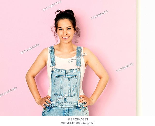 Portrait of young smiling woman with black hair and hands on hips in front of pink background