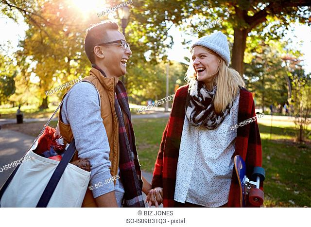 Young female skateboarder laughing with boyfriend in park