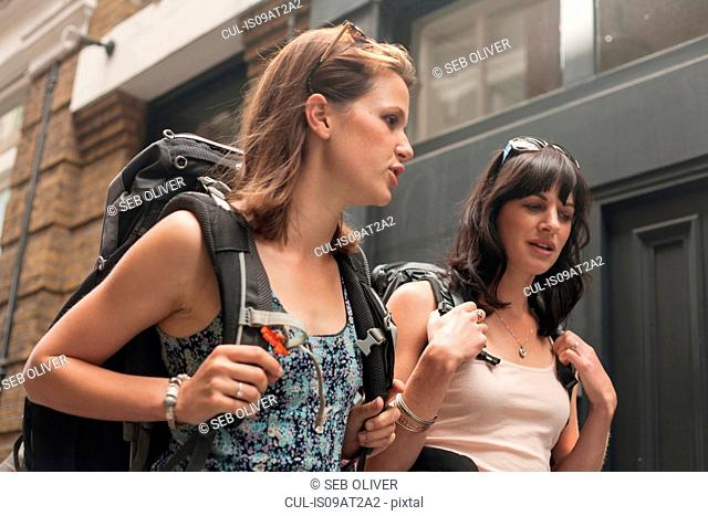 Two women backpackers chatting whilst strolling along street