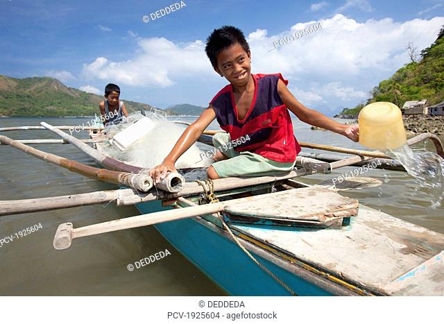 two young filipino boys work on their family's wooden bangka boat in the tiny fishing village of vigan near snake island and el nido, vigan, bacuit archipelago