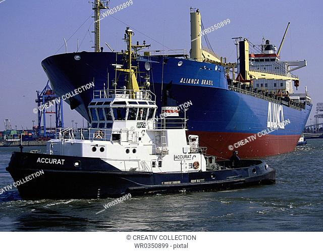 navigation ship leading a big cargo ship out from a harbour