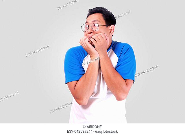 Portrait of young funny Asian man biting his nails as if he is worried afraid of something bad