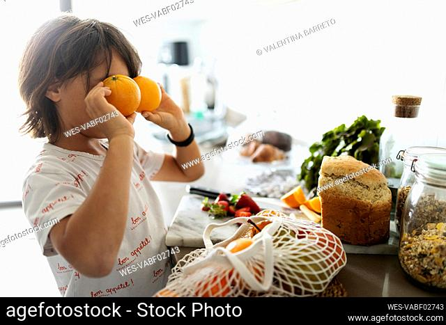 Boy in kitchen covering eyes with oranges