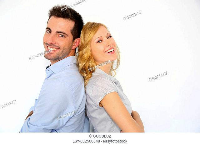 Cheerful couple standing back to back on white background