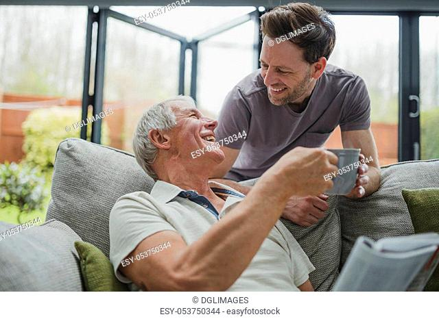 Man is leaning over the sofa to give his father a cup of tea. He is sitting on the sofa and is taking it from him gratefully