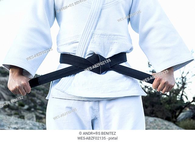 Man tying his black belt during a martial arts training