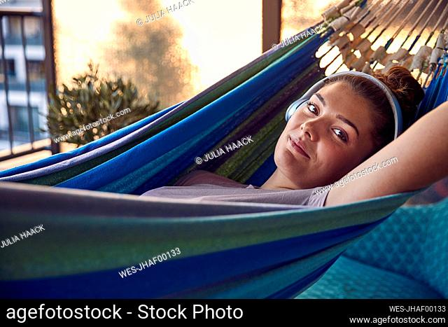 Portrait of smiling young woman lying on hammock on balcony listening music with headphones