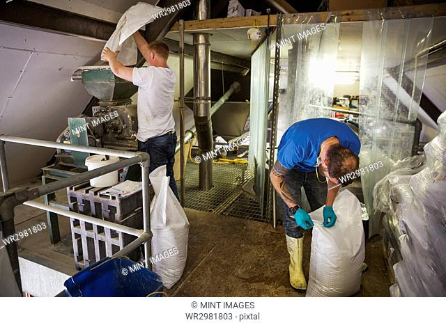 Two men working in a brewery, holding white plastic sacks
