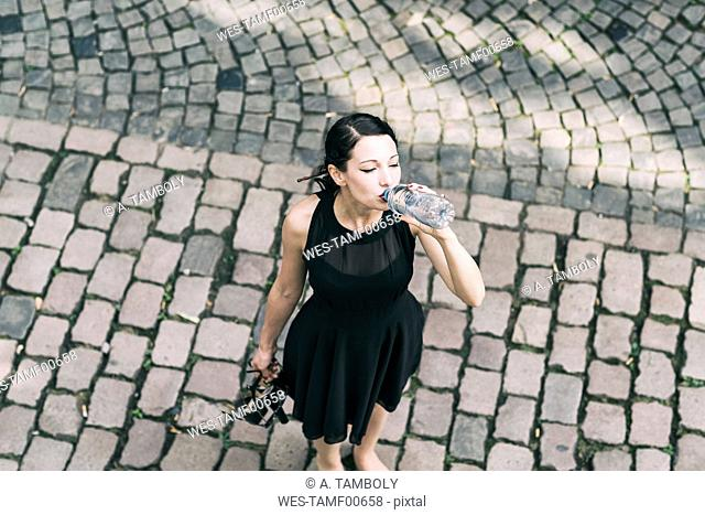 Young woman standing on cobblestones drinking water from bottle