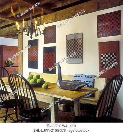 EATING AREA - Checkerboards on wall. Antique table, goose decoy, punched tin chandelier, bowl of hedge apples, bench , quilt, exposed beams
