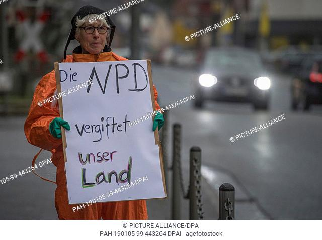"05 January 2019, Hessen, Büdingen: """"The NPD poisons our country"""" is written on the poster of a counter-demonstrator who has positioned herself on the through..."