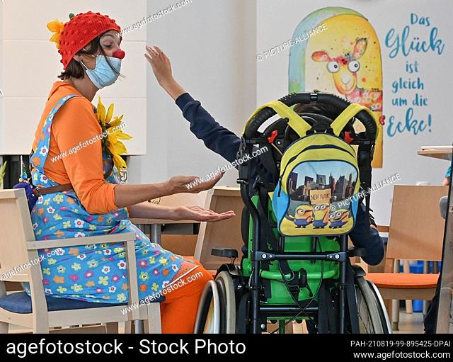 19 August 2021, Brandenburg, Burg: The clown Pepina Peppich from Lachen hilft e.V. takes care of a child in a wheelchair at the children's hospice...