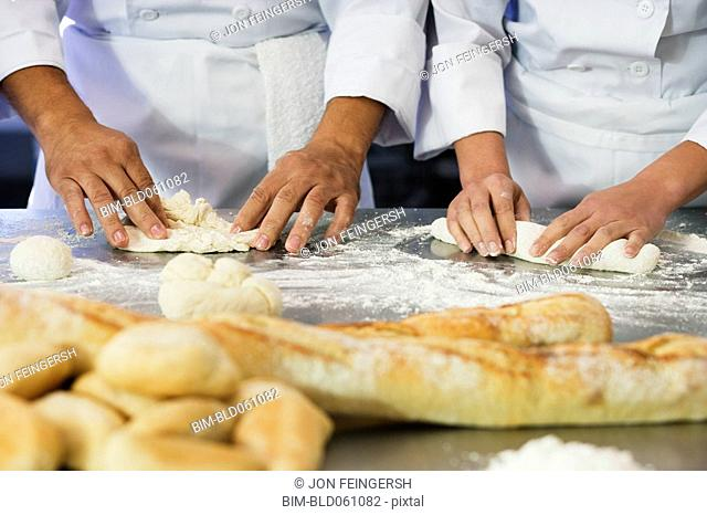 Close up of bakers rolling dough