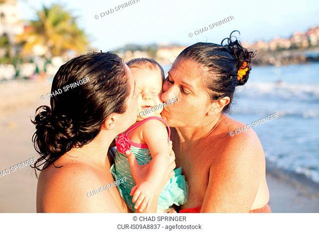 Grandmother, daughter and baby granddaughter on beach, St Maarten, Netherlands