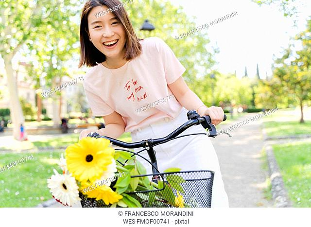 Portrait of happy young woman with flowers and bicycle in park