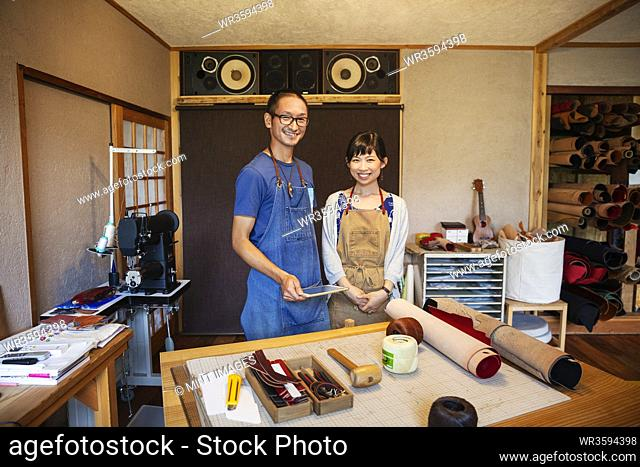 Japanese woman and man wearing blue apron and glasses standing in a leather shop, smiling at camera