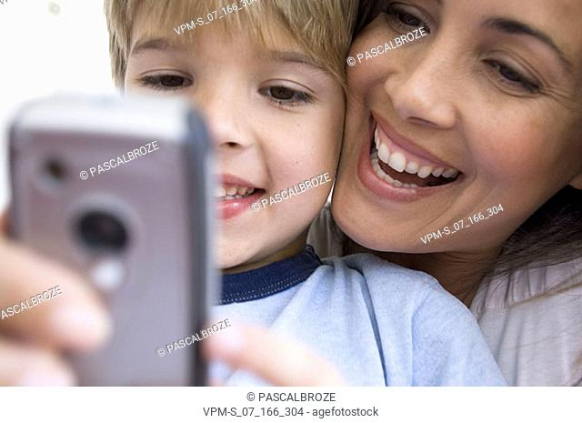 Close-up of a boy holding a mobile phone with his mother