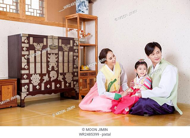 Smiling girl and her parents in traditional Korean clothes