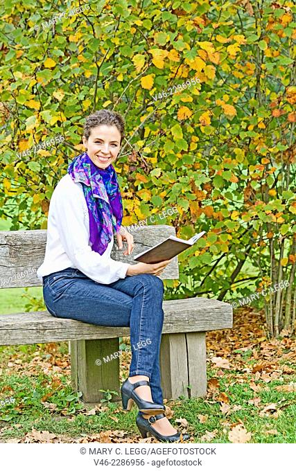 Woman on a park bench with book. Woman in white blouse with blue scarf and blue jeans is sitting on bench in a park