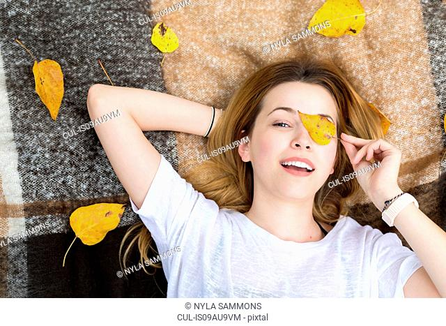 Young woman lying on blanket, covering eye with leaf