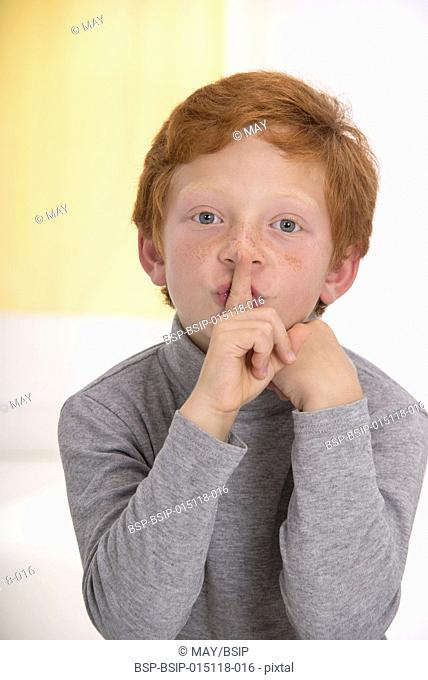 Boy with finger on his lips