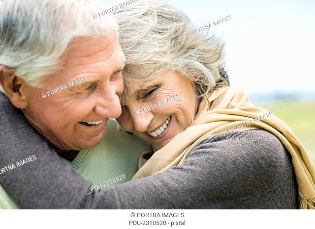 Close-up of happy senior couple embracing in park