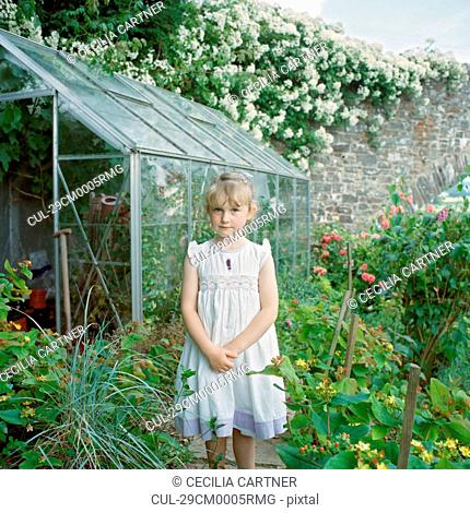 Little girl standing by greenhouse