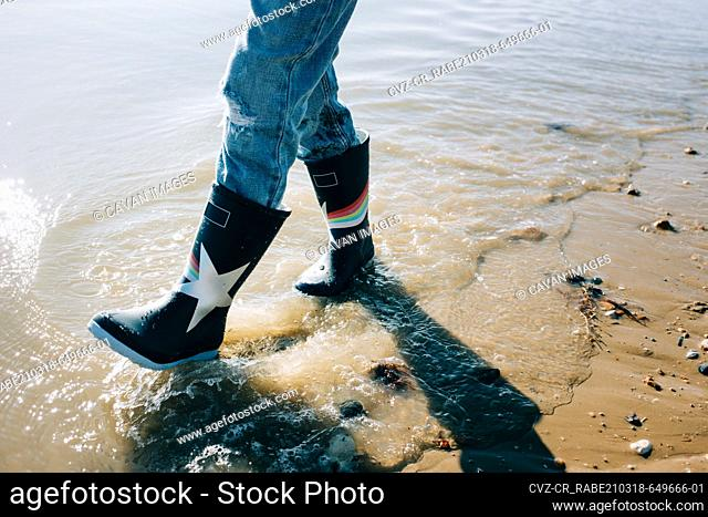 kids rain boots walking through the sea on a sunny day in England