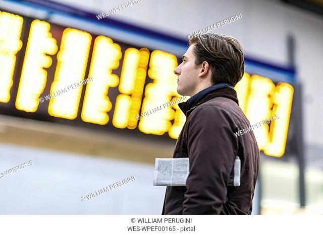 UK, London, businessman at train station looking at timetable
