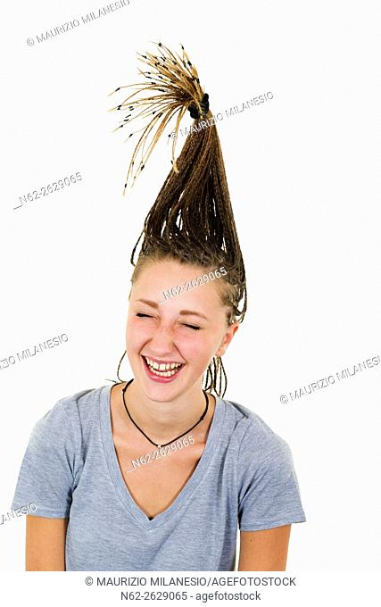 Very cheerful blonde girl laughs vigorously her tresses are raised vertically on her head