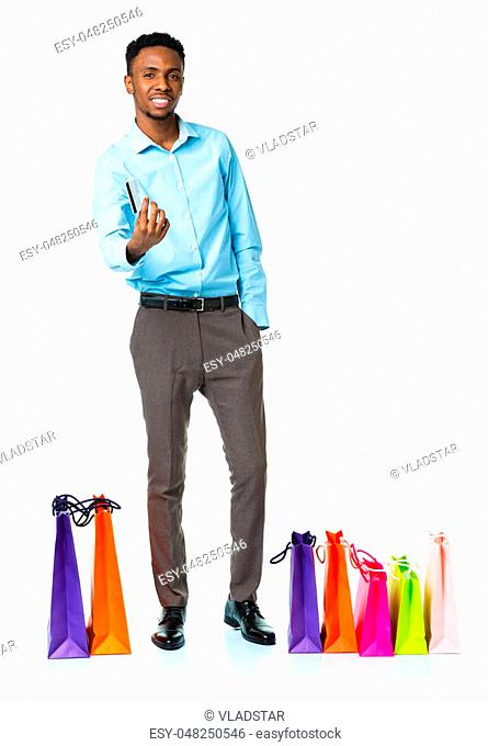 Happy african american man with shopping bags and holding credit card on white background. Christmas and holidays concept