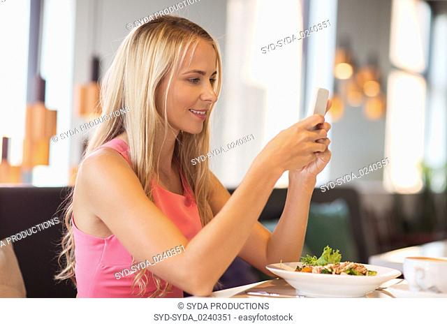 happy woman with smartphone eating at restaurant